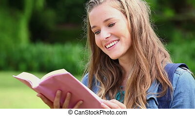 Happy woman reading a fascinating book