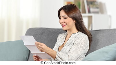 Happy woman reading a letter at home - Happy woman reading a...
