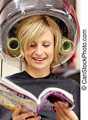 Happy woman reading a magazine with hair curlers under a hairdryer in a hairdressing salon
