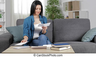 Happy woman reading a receipt at home