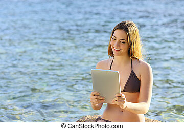 Happy woman reading a tablet reader on the beach seaside