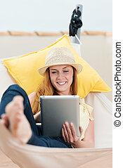 Happy Woman Reading EBook In Hammock