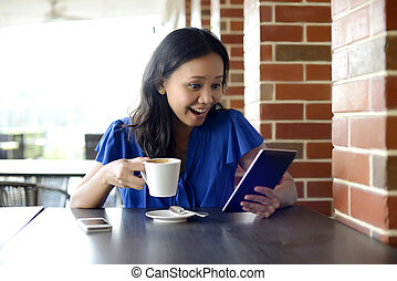 Happy woman reading email in Cafe