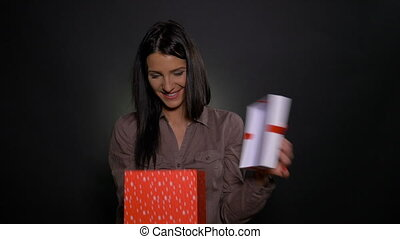 Happy woman receives a big gift box with a smaller gift box inside and is surprised and excited