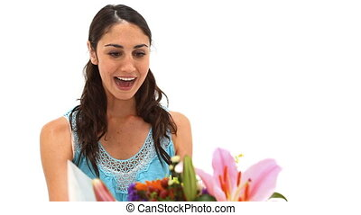 Happy woman receiving a bunch of flowers against a white...