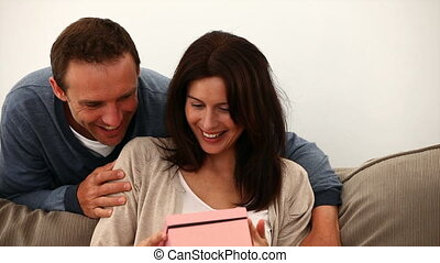 Happy woman receiving a gift from her boyfriend in the living room