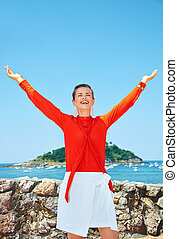 Happy woman rejoicing in front of scenery overlooking lagoon