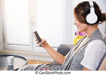 Happy woman relaxing at home listening music