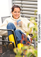 Happy woman relaxing cup tea sitting backyard