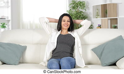 Happy woman relaxing sitting on a couch at home - Front view...