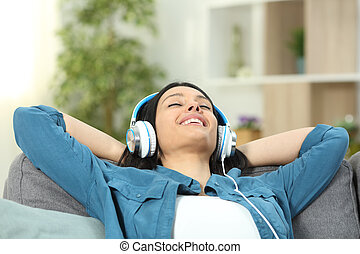 Happy woman resting listening to music on a couch
