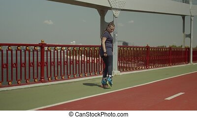 Happy woman rollerblading backwards on river bridge - Young...