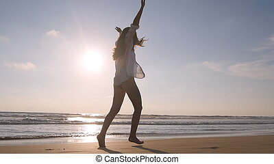 Happy woman running and spinning on the beach near the ocean. Young beautiful girl enjoying life and having fun at sea shore. Summer vacation or holiday. Nature landscape at background