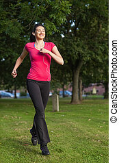 Happy woman running in a green park