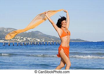 happy woman running on beach on vacation in mallorca