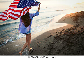 Happy woman smiling and running on beach while celebrateing independence day and enjoying freedom in USA