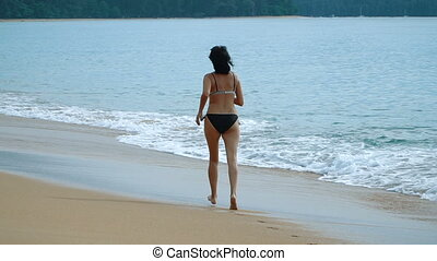 happy woman running on the exotic beach in the summertime