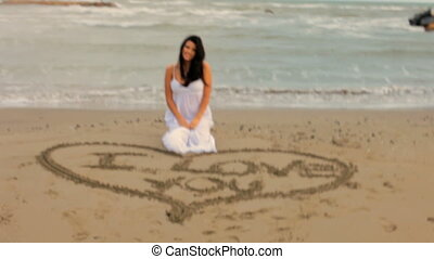 Woman in a storm saying I love you to the camera on a beach