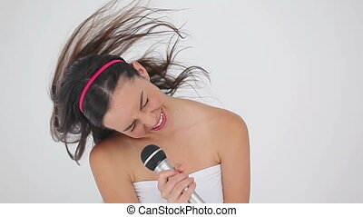 Happy woman shaking her hair while singing