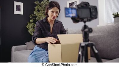 Happy woman shooting unpacking video on camera - Happy woman...