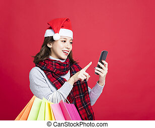 happy Woman shopping for christmas gifts by smart phone