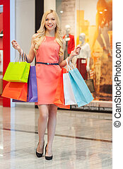 Happy woman shopping. Full length of young beautiful shopping woman smiling with colorful bags at mall center
