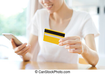 Happy woman shopping online with a credit card and a phone