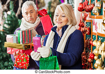 Happy Woman Shopping Presents With Tired Man - Happy senior...