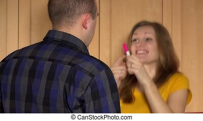 Happy woman show pregnancy test for lover and upset man walk away.