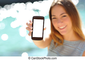 Happy woman showing a blank smartphone on the beach with the...