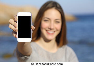 Happy woman showing a smart phone display on the beach with the sea in the background