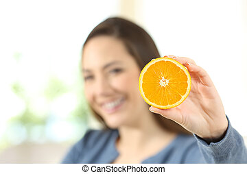 Happy woman showing an orange