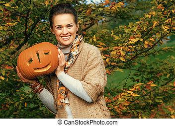 happy woman showing Halloween pumpkin Jack O'Lantern