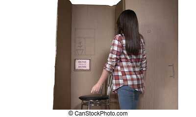 Happy woman showing keys of her new apartment moving into tiny cardboard box