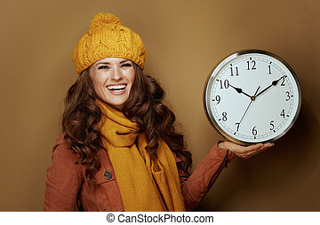 happy woman showing round clock remind about fall time change