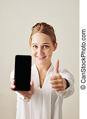 Happy woman showing smartphone
