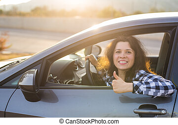 Happy woman showing thumb up and driving a new car