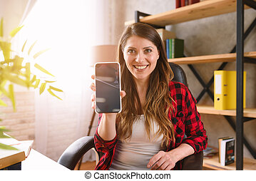 Happy woman shows something in her modern smartphone