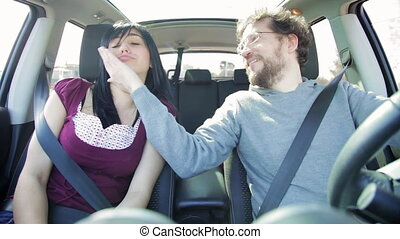 Happy woman singing in car with boyfriend smiling