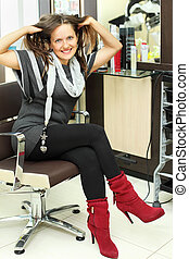 Happy woman sits in armchair and touches her hair in beauty salon