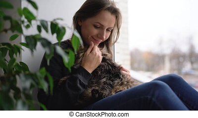 Happy woman sits on the window sill with a cat on her lap and strokes her fluffy fur