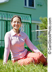 Happy woman sitting against home