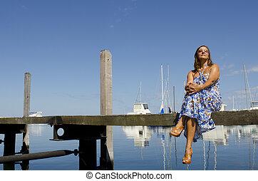 Happy woman sitting at marina