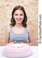 Happy woman sitting at the table with cake