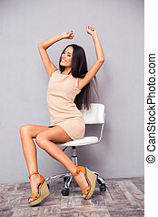 Happy woman sitting in office chair