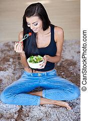 Happy Woman Sitting on Floor Eating Fresh Salad