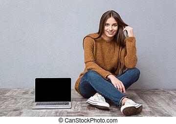 Happy woman sitting on floor near laptop with blank screen