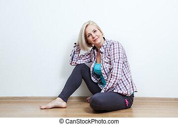 Happy woman sitting on floor with crossed legs.