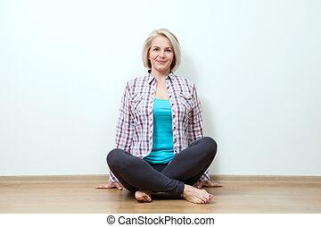 Happy woman sitting on floor with crossed legs in studio