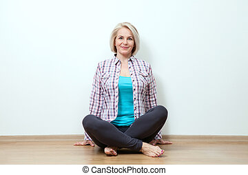 Happy woman sitting on floor with crossed legs in studio